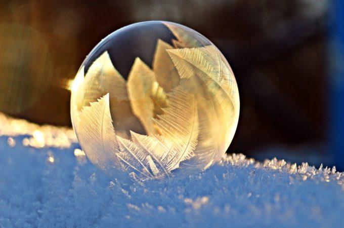Eine Seifenblase von einem Frostmuster bedeckt wird von der Sonne angeschienen.